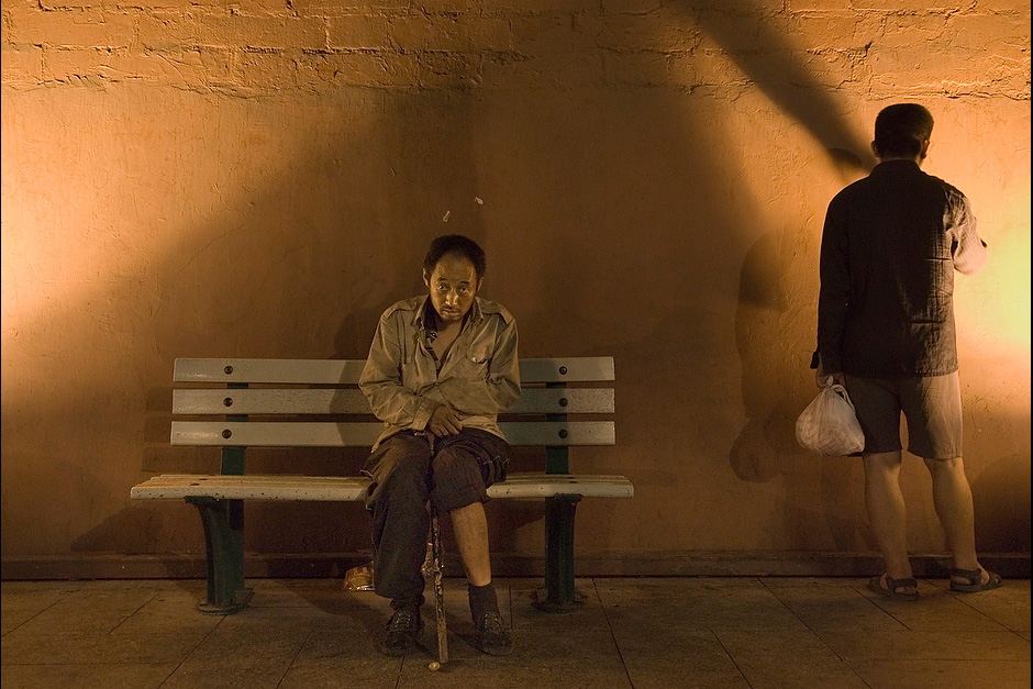 A homeless man sitting on a bench next to Chang'an Jie in Beijing.
