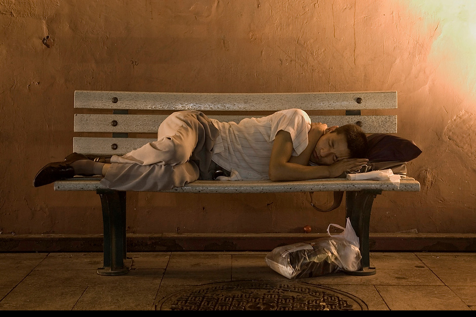 A man sleeping on a bench.
