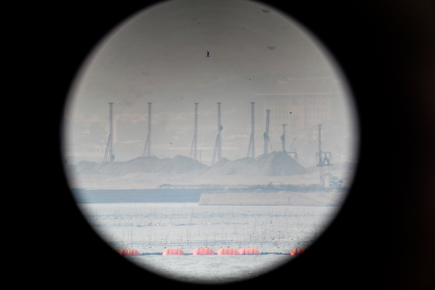 Viewed through binoculars from the Mashan Observation Station on Kinmen, pile drivers rise above sand dunes on China's Dadeng Island, the closest point in mainland China to Kinmen, and the proposed site of nearby Xiamen's new airport.