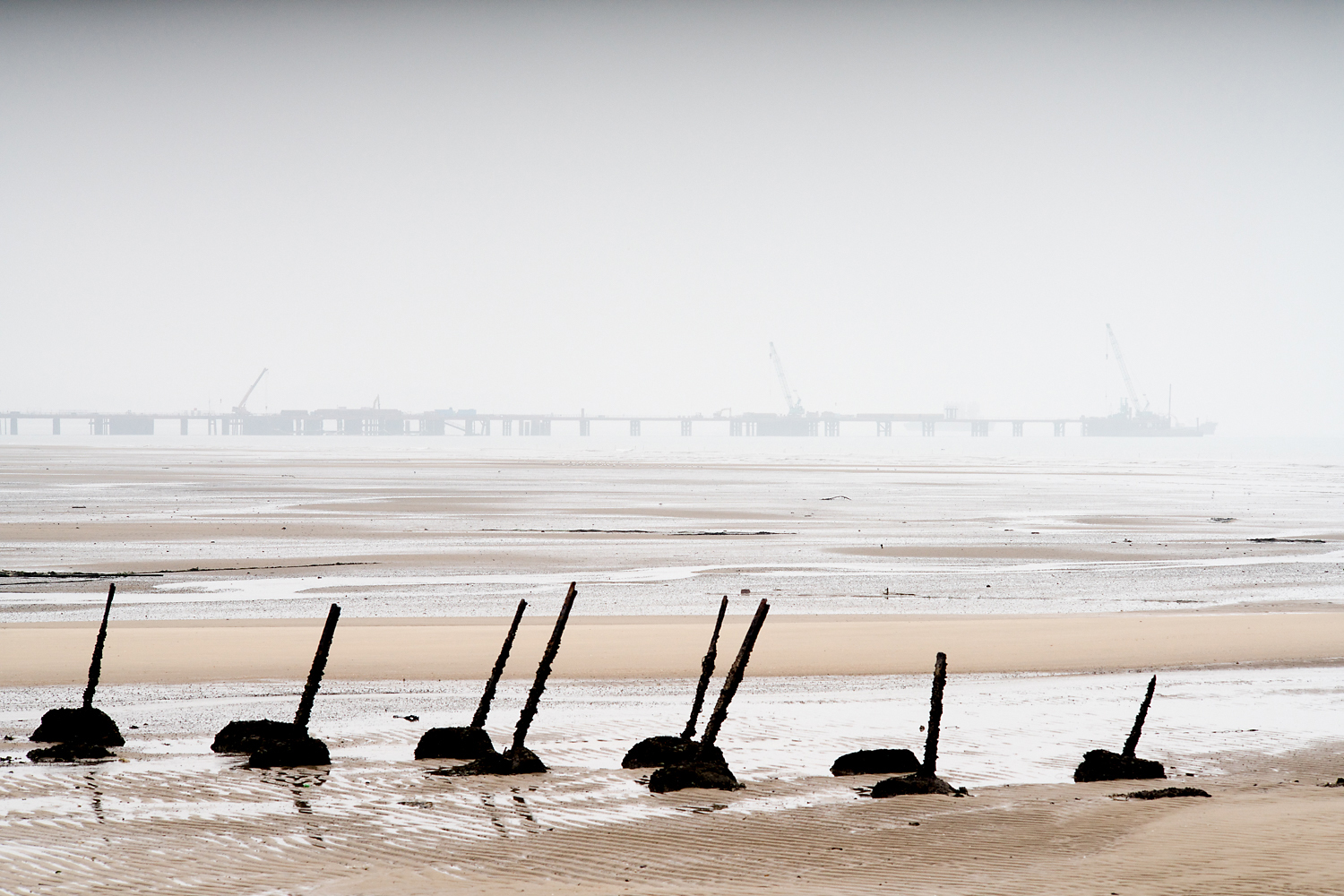 A foggy view of the bridge being built between Kinmen and Lieyu Island, seen from Kinmen's spike-lined northwest coast at low tide. One villager said, 'What's the point if the bridge goes only to Little Kinmen, which has nothing? It must link directly to Xiamen; only then is it a useful bridge. Goods and people can flow. But that's a long way away in the future.'