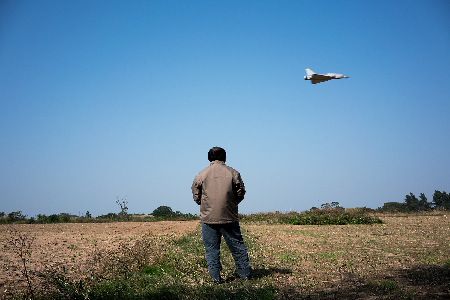 A miniature, battery-operated Dassault Mirage 2000 fighter jet—a scale model of the ones the Taiwan Air Force uses—zooms past an open field in Kinmen. Piloting it is Chen Minghan, an air conditioner repair man originally from mainland Taiwan. He said, 'People ask me if it's good to reunite with mainland China. I say it's now not good but in the future it might be good. There is a better quality of life and more freedom here, even if we are more backward compared to China. Their smog is blowing over there. China is so big and Taiwan is so small. If every person in China spat, it would flood all of Taiwan!'