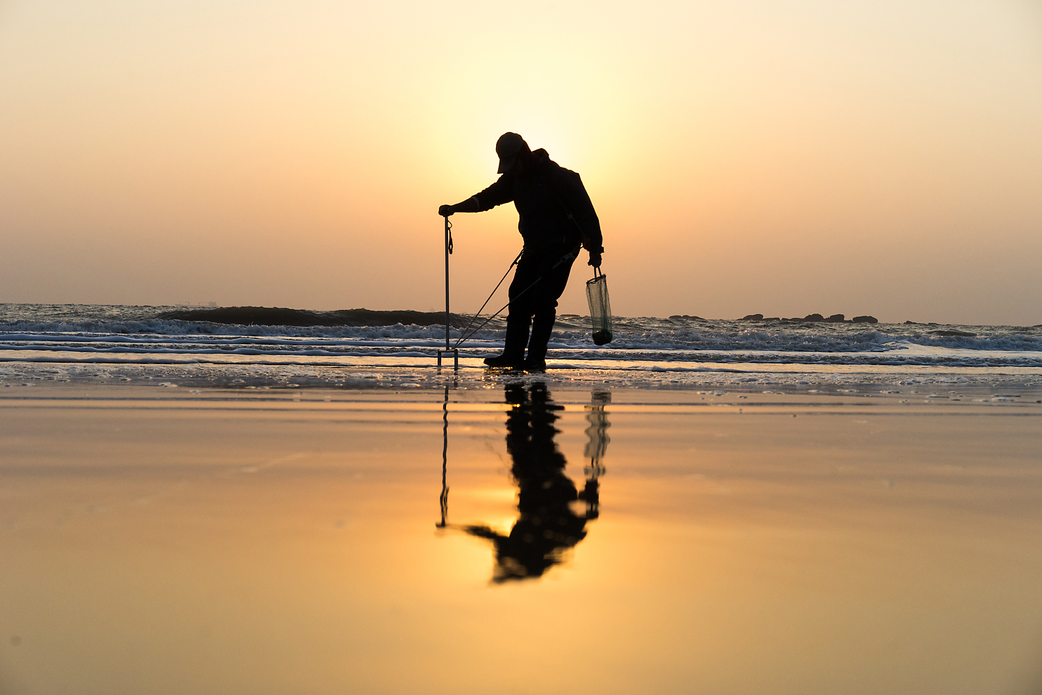 A villager on Kinmen's southwestern coast combs the beach at sunrise as the tide recedes. It was only in 2013 that Kinmen was declared free of mines. Tens of thousands of mines were planted in the '50s and '60s at the height of tension between Taiwan and the People's Republic of China. The island was ruled as a military base until 1992 and was subjected to 'frogman' attacks and regular Chinese shelling. The mine-laden beaches and military rules restricting locals from swimming or going near coastal areas where the army was stationed have left Kinmen residents with a complex feeling towards the sea. Many residents cannot swim and still have a fear of the water for all the negative imagery it conjures.