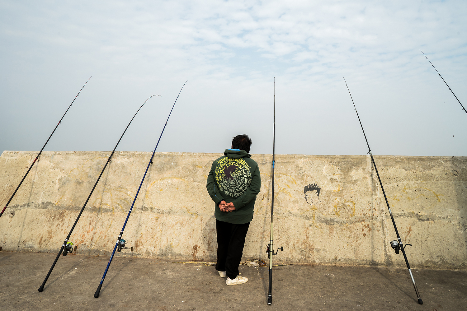 An angler waits for a bite at an embankment near the Shuitou ferry terminal. The embankment was built alongside the ferry terminal and lighthouses on reclaimed land and part of what was formerly a fishing village. Some local residents from the village protested the development, which made them lose their natural port and fishing livelihood and also harmed the habitat of the horseshoe crab.