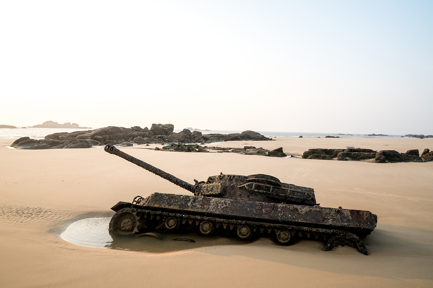 A military tank, half buried in the sand on a beach, is visible at low tide in Kinmen. The island was managed as a military base from 1949 until 1992, when martial law was lifted. KMT leader Chiang Kai-shek stationed a significant portion of his army on Kinmen, planning to retake mainland China from there. At the height of the Cold War, as many as 100,000 soldiers were barracked on Kinmen, outnumbering civilians. Today, there are only about 3,000 troops left on the island.
