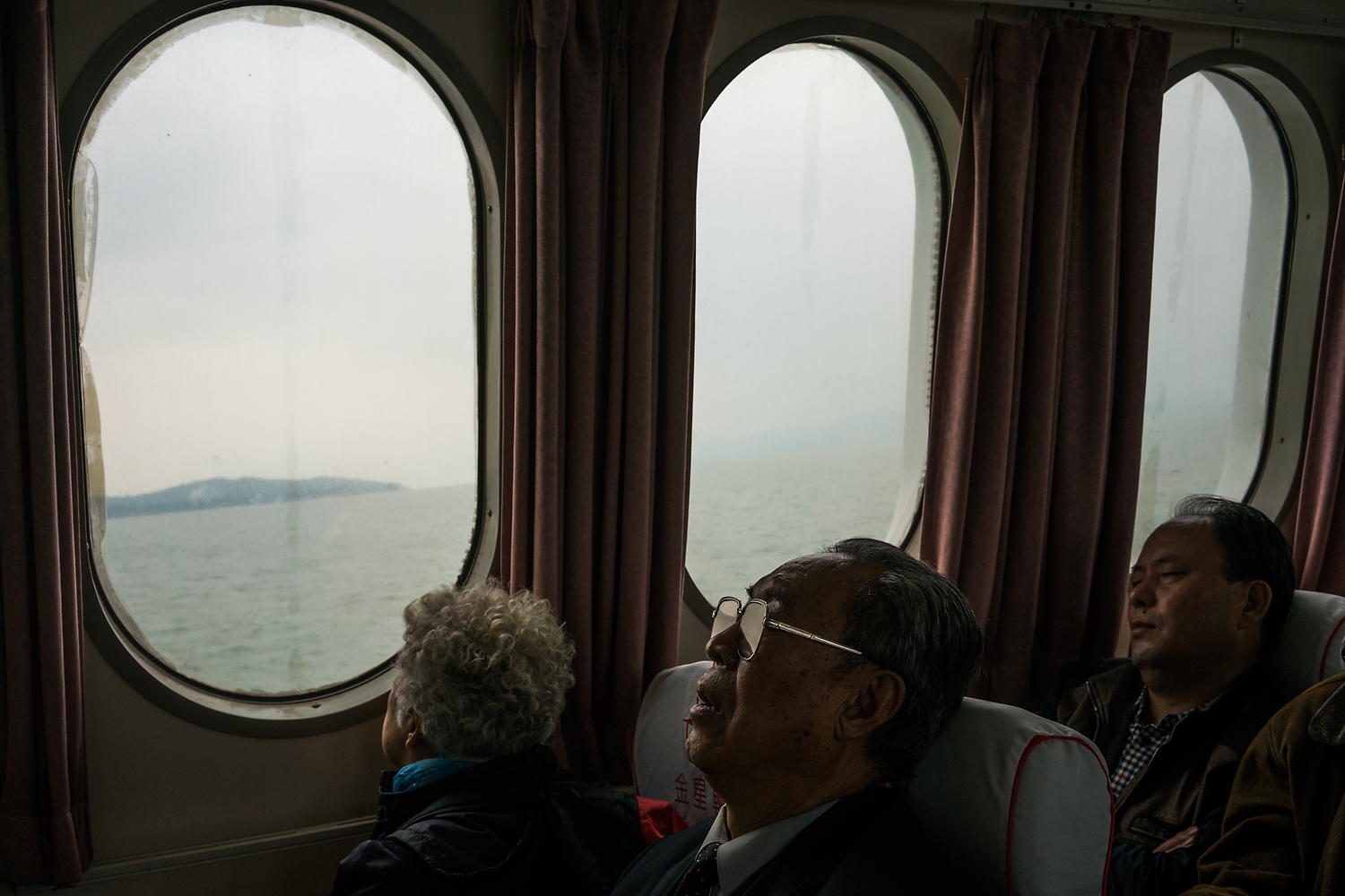 On the 30-minute ferry ride from Xiamen's Wutong ferry terminal to Kinmen, an elderly mainland Chinese tourist takes a nap while his female companion looks out the window as the boat crosses from Chinese to Taiwanese territory in the Taiwan Strait. The ferries were launched as part of the 'Mini-Three-Links' between China and Taiwan in 2001. More than 1.5 million passengers traveled by ferry in 2014 between Fujian, in China, and Kinmen. Since 2015, Chinese tourists traveling to Kinmen can easily get visas on arrival, a move to encourage mainland Chinese tourism.