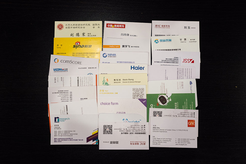 A display of business cards collected by Ji over the course of an hour are splayed out on a table. He believes that knowing a lot of people will prove advantageous for his future.  (Photo by Yuyang Liu)