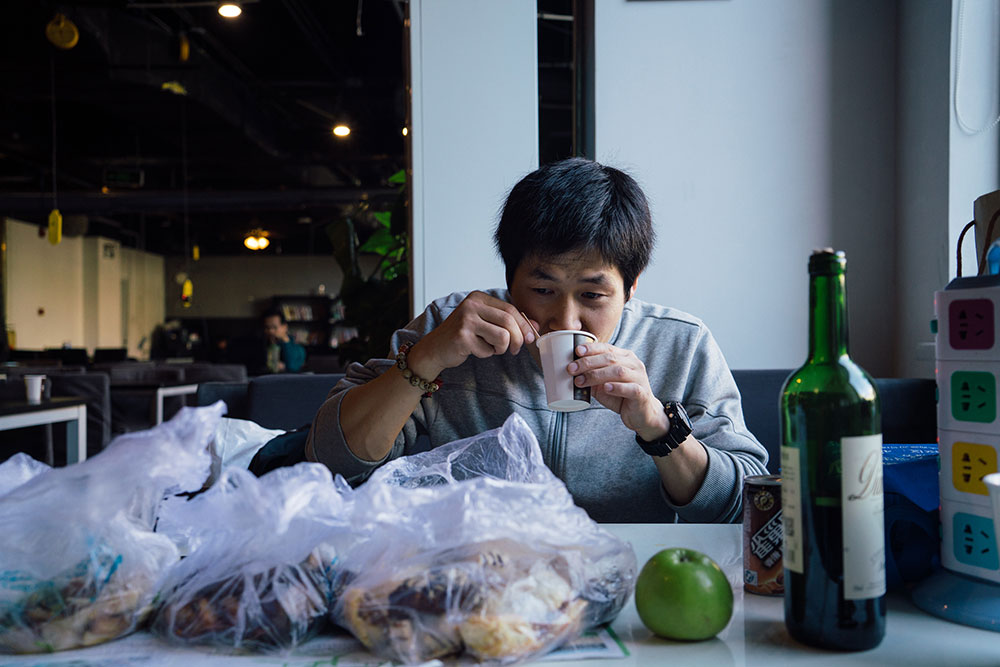 Ji Yu, from Henan province, eats a breakfast of leftovers from a meeting he had the previous day. He says he feels that at The Garage and in Zhongguancun generally, you can always meet a new person or learn something new. (Photo by Yuyang Liu)