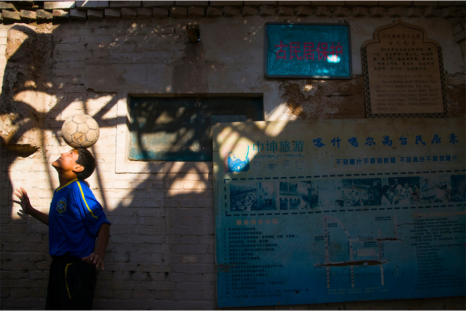 "In the old city of Kashgar, a descendant of seven generations of Uighur potters balances a soccer ball in the alleyway in front of his house. The ""beautiful game"" first came to Xinjiang province in the nineteenth century."