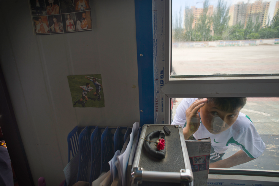 Dilmurat, who, like many Uighur goes by only one name, looks through a window while waiting for a friend. An outstanding goalie, Dilmurat has passed a qualifying test to the prestigious Evergrande Football School in Guangdong province, a requirement for acceptance. His father often drops by the school to watch him play.