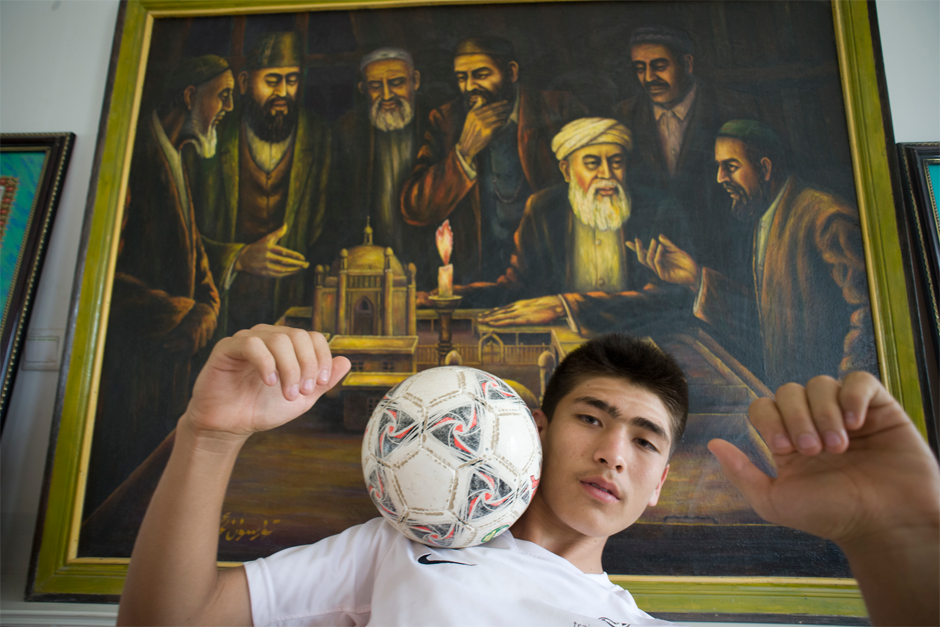 Imran, a young soccer player from Artux, poses in front of an oil painting in the school's museum, which shows his ancestors debating the reform of traditional religious education. He recently spent a month in Italy training with the Juventus Football Club, and this is his first visit to Iksak, a place of great significance for Uighur soccer players.