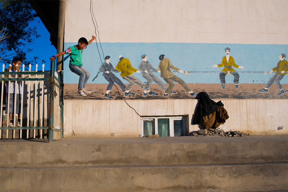 A child jumps the fence of a recreation area to play soccer in Ahu Township, near Artux. Coach Nasrulla Mijit says that Iksak and the surrounding areas are rich with promising players. Surveys show that Artux has produced far more professional athletes than many larger cities elsewhere in China.