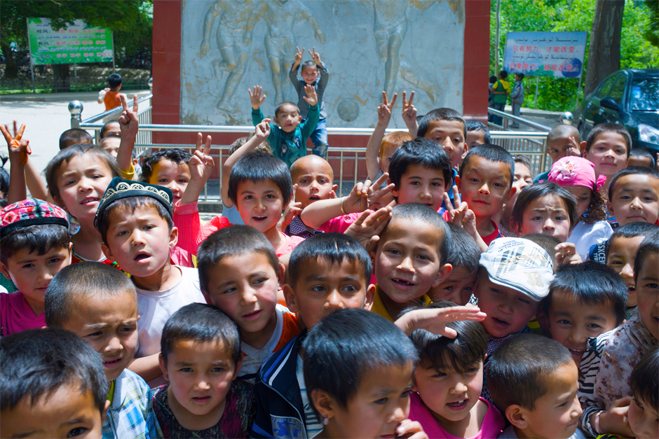 Elementary school children surround the statues of Hussein and Bawudun Musabayov, founding fathers of the town's soccer tradition in Iksak, a town near the city of Artux. In 1874, the two brothers began an audacious plan to reform madrassa schools by incorporating elements of modern Western education, including training in soccer.
