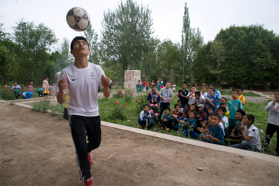 Imran demonstrates soccer techniques for students in front of Iksak Elementary School's soccer monument. After 1885, when the Musabayov brothers founded the region's first modern school, history, geography, and Farsi were added to the school's curriculum, and soccer became a required course.
