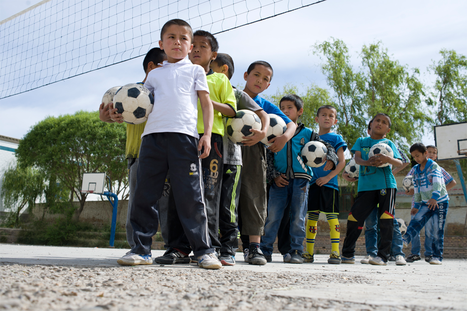 Young soccer players wait for their turn to practice at a rural elementary school near Artux. Club teams, more government funding, and targeted assistance from partner provinces and municipalities arranged by the central government could allow more talented soccer players to make it big.