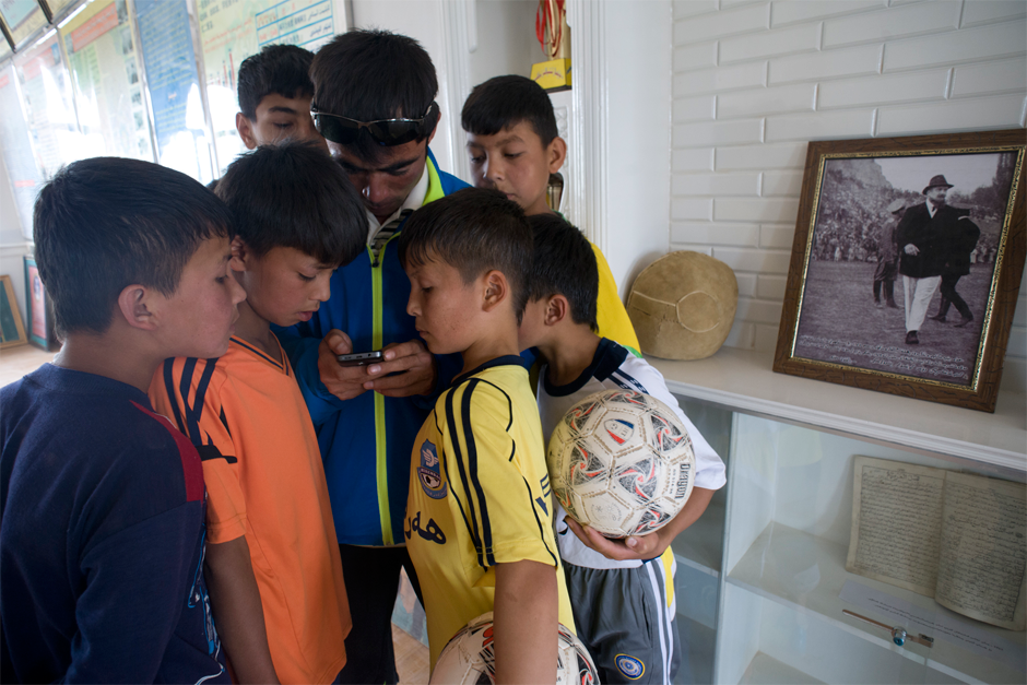 A hand-sewn sheepskin soccer ball commemorating the villagers' victory over the British and Swedish teams in 1927 is on display in a museum at Iksak Elementary School. Coach Ekber, born and raised in a town with a rich soccer history, shares a photograph on his cellphone of his grandfather playing soccer when he was young.