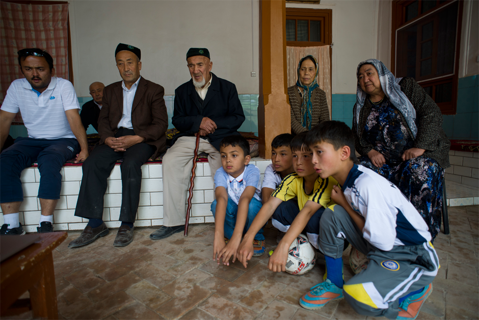 Guests at Memet Zunun's house watch a documentary about soccer players from Urumqi's Fifth Elementary School. Zunun has 48 soccer-loving grandchildren, eleven of whom have played on professional teams.