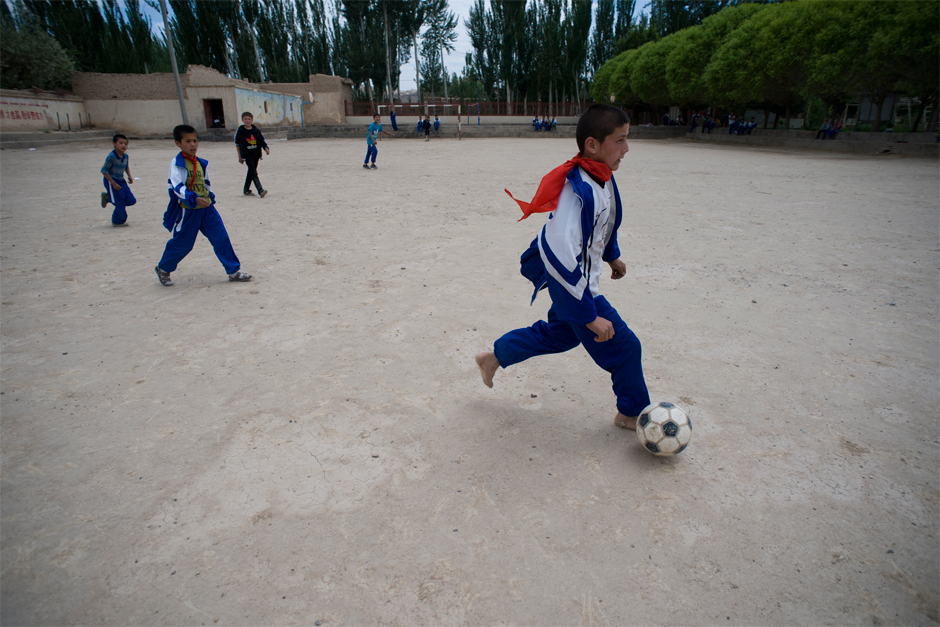 At an elementary school in Meyi Village, Azak Township, a student plays soccer barefoot on a dirt playing field.