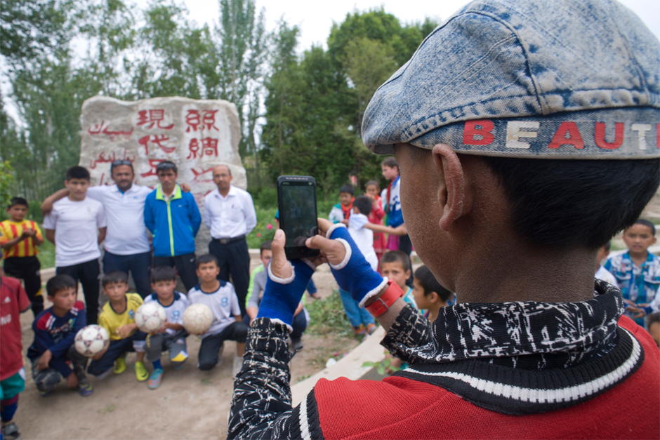 """A stone monument in front of Iksak Elementary School reads: """"Birthplace of Modern Soccer on the Silk Road."""""""