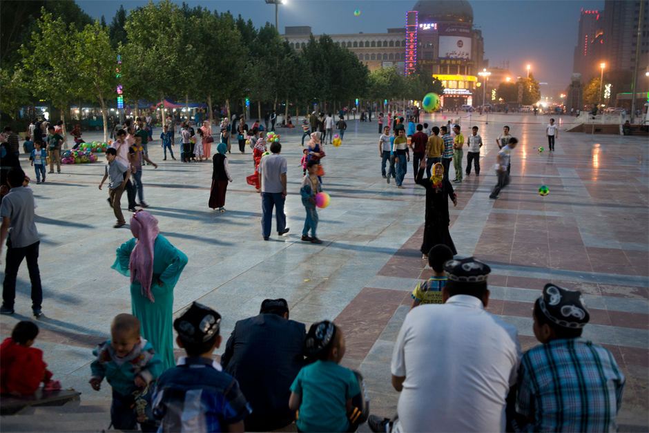 In the central plaza of Hotan city, people of all ages play soccer as dusk falls.