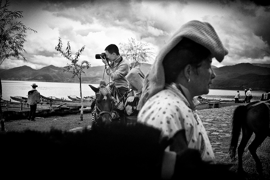 Tourists take pony rides led by Mosuo women at Lugu Lake. Yunnan, China.