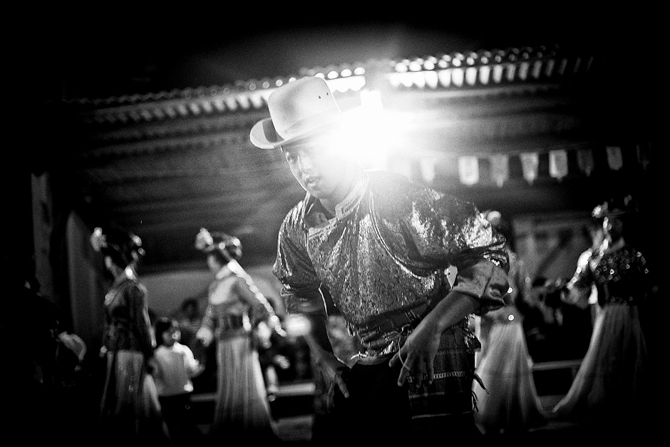 The Cauldron Fire Evening is a nightly song-and-dance session performed by the Mosuo for tourists. About thirty dancers participate and engage with the audience in traditional Mosuo folk performances. They charge thirty yuan a person and share the proceeds equally among all performers. Luoshui, Yunnan, China.