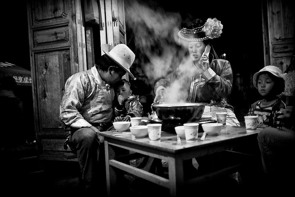 "Zha Ba and Na Zhu have supper with their daughter, La Mu, and Na Zhu's family after performing at the Mosuo Cauldron Fire Evening. Although they practice ""walking marriage,"" Zha Ba gets to see his daughter frequently, unlike most Mosuo men in previous generations. Luoshui, Yunnan, China."
