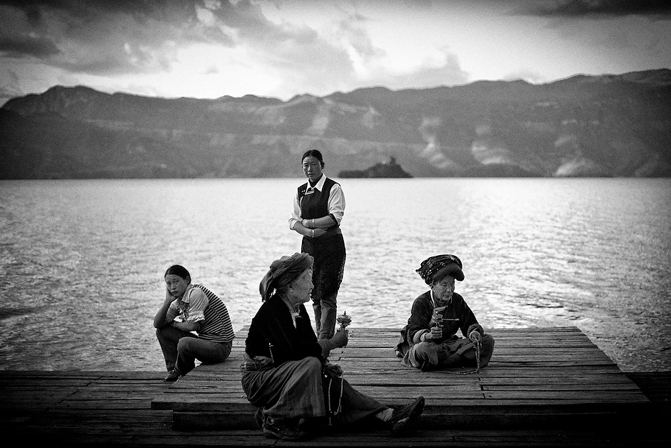 Mosuo women rest by Lugu Lake, some spinning prayer wheels. Despite the development around Luoshui, Mosuo women continue their traditional way of life, emphasizing a culture revolving around large matriarchal families and practice of Tibetan Buddhism. Luoshui, Yunnan, China.