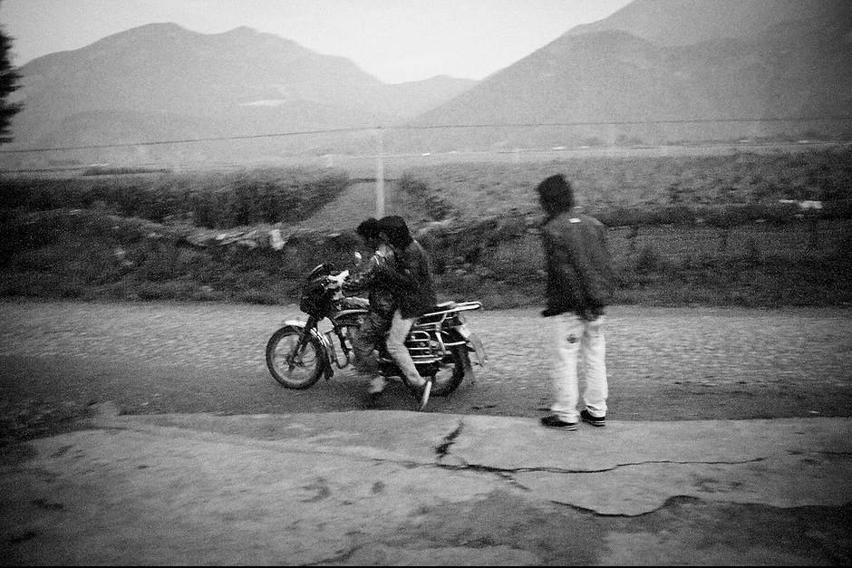 "Young men gather outside the only provision shop at dusk before heading to their ""walking marriages."" These days, men whose partners live too far to walk typically ride motorcycles instead. Zha Xi, 22, heads off to the hot springs before seeing his lover. Aguwa, Yunnan, China."
