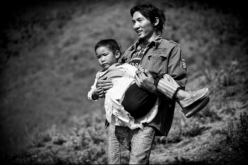 "Su Na Dorje, 26, takes his two nieces up the hill to the village shrine to worship. As the maternal uncle, Su Na has to play the role of father to the two girls, Zhi Ma La Zu, 8, and Zha Xi Yi Zong, 4. In the matrilineal Mosuo culture, uncles serve as fathers to keep the family structure intact. Women rule the roost, while their brothers practice ""walking marriage."" The men are not allowed to set up their own families, but instead stay within their extended families as shared father figures. Aguwa, Yunnan, China."