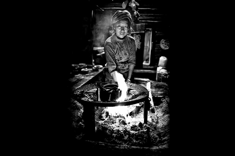 Ci Er Zu Ma, 40, wife of Song Nang Da Zhu, 49. The Mosuo life revolves largely around the hearth, which is used for cooking, warming up, and smoking. Wujiu, Sichuan, China.