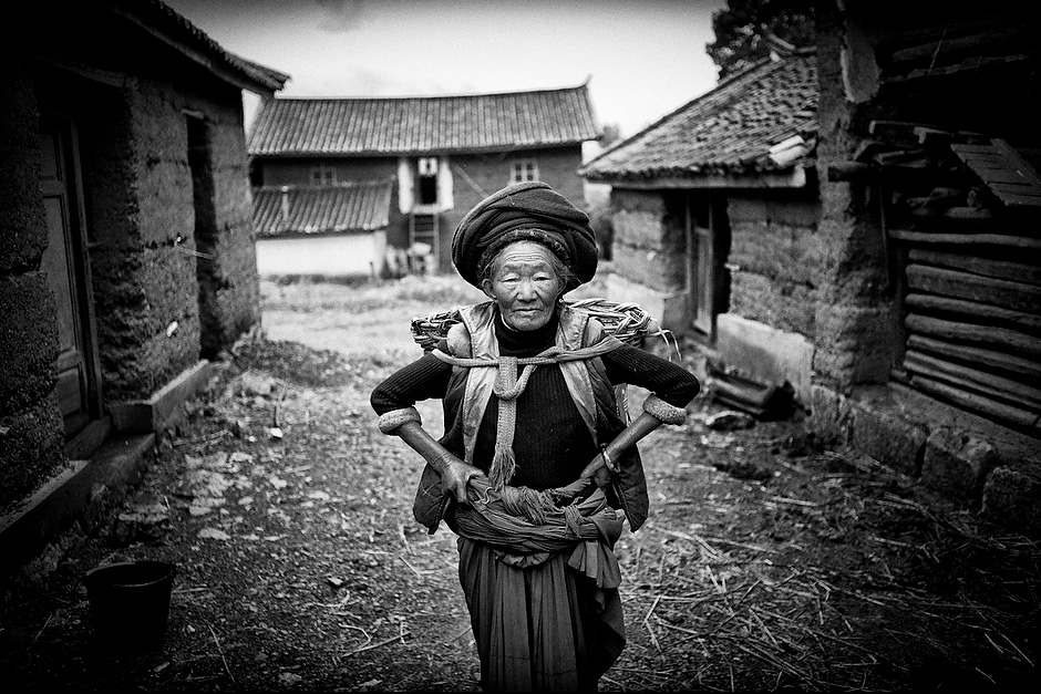 Cier Zhima, 73, the matriarch of a Mosuo household, poses for a picture before heading off once again for the fields. Aguwa, Yunnan, China.