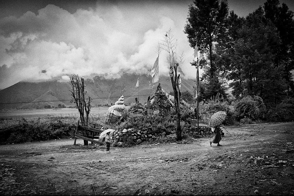 Mosuo matriarch Guzu Lazu, 70, carries her two-year-old granddaughter, Senu, while another granddaughter, Songnang Lamu, 5, follows. Aguwa, Yunnan, China.
