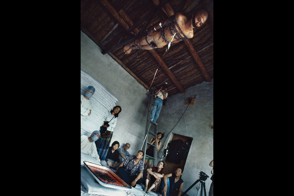June 1994. Zhang Huan at his East Village home performing <em>65 Kilograms</em>. Actually, this was the first of a string of performances that included Ma Liuming and Zhu Ming. The first day was Zhang, the second day was Ma, and the third day was Zhu. More than twenty people came, including some artists, friends, curators, and foreigners (among whom were Germans and Japanese). Zhang's performance went extraordinarily smoothly from start to finish.