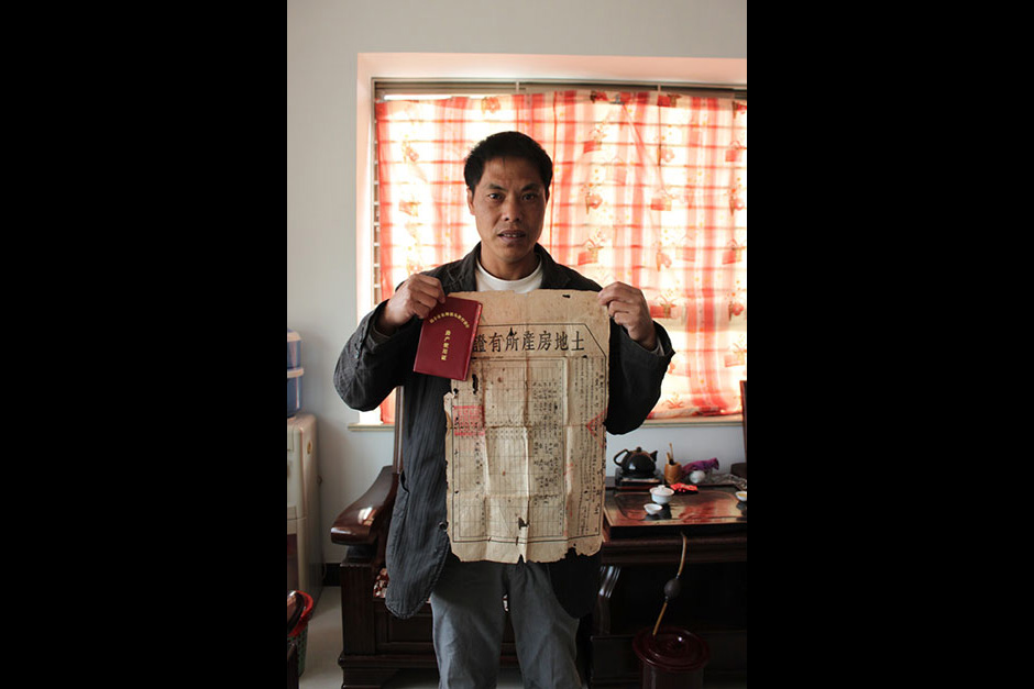 Villager Zhang Bingchai holds his land-lease contract and house property certificate in his home in Wukan.