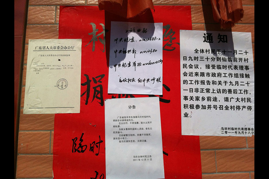 Postings outside the Village Party Committee house include phone numbers to contact and petition the government, Xue Jinbo's obituary, and a call for a general strike. The poster in the background is asking for donations to support the villagers.