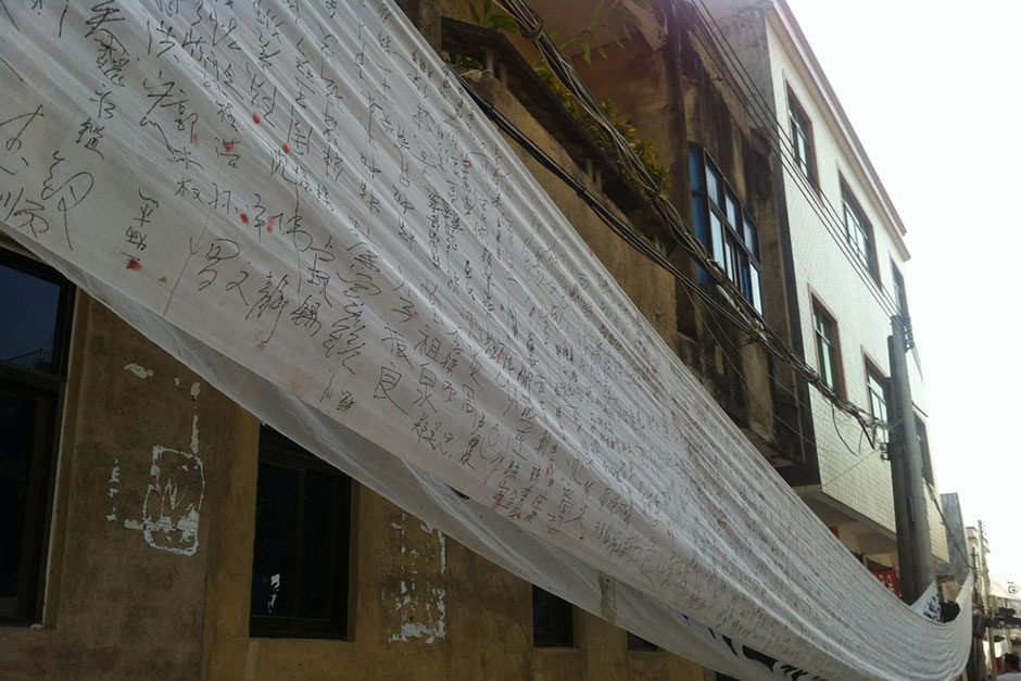 A banner hangs along the city street with villagers' signatures petitioning government officials at higher levels.