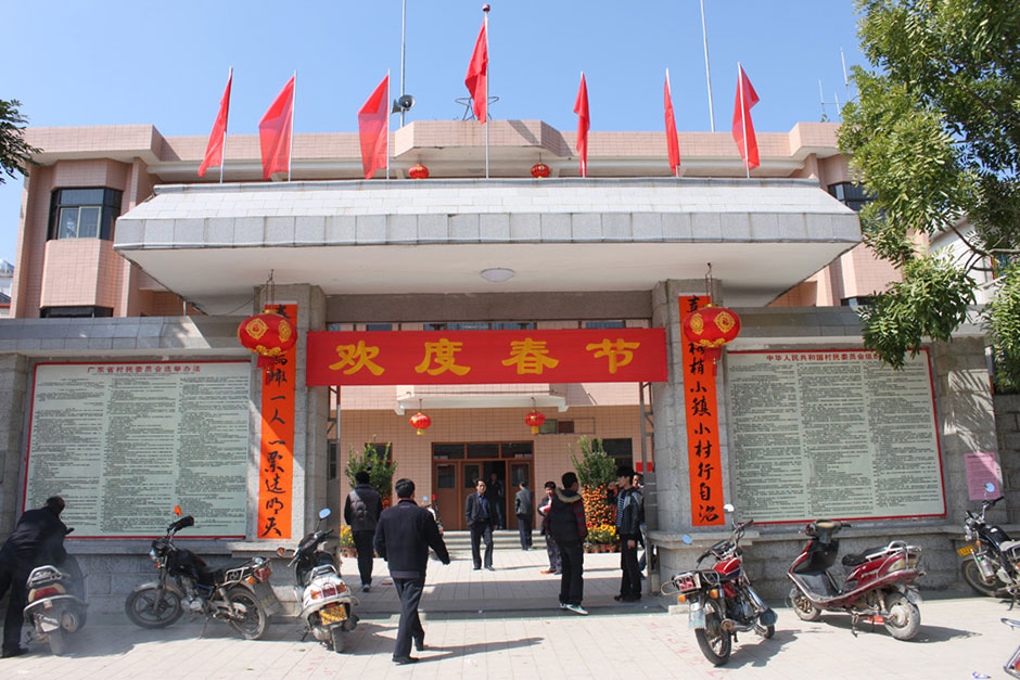 "On the eve of the Chinese New Year, couplets (ceremonial banners) are posted outside the Village Party Committee office. The couplets were contributed by a netizen and calligraphed by protest leader Yang Semao. The translation reads: ""Small village starts self-governance with great happiness showing in our eyes, tomorrow will be determined by 'one person, one vote' while spring is coming back to Wukan."""