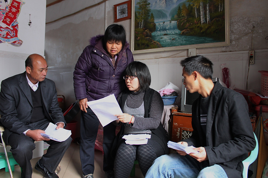 Chen Suzhuan (seated), a Wukan villager and activist, distributes ballot voting certificates and explains the voting process to villagers in Wukan, January 30, 2012.
