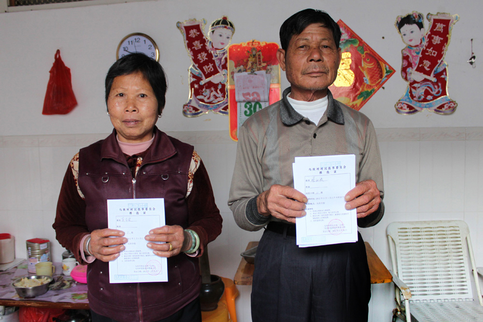 A married couple display their ballot voting certificates inside their Wukan home, January 30, 2012.