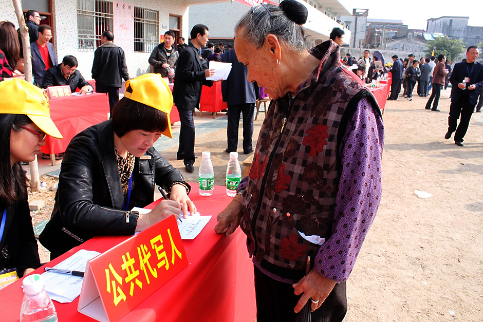 Ou Aiping (second from left), a teacher from Wukan Primary School, helps Lin Qu, who is illiterate, with Lin's ballot during polling, February 1, 2012.