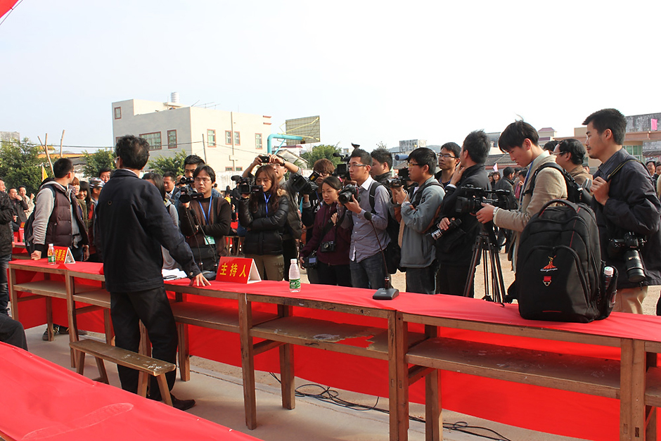 Lin Zuluan (back to the camera) stands in front of journalists and photographers waiting to hear word of the first round of election voter results in Wukan, February 1, 2012.