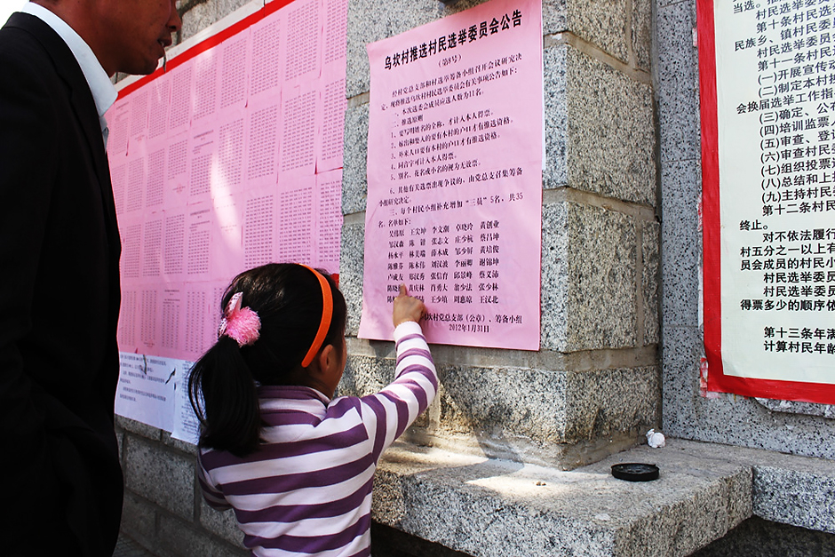 A village girl helps her father identify his name from a list of voters posted outside the Village Party Committee office, January 31, 2012.