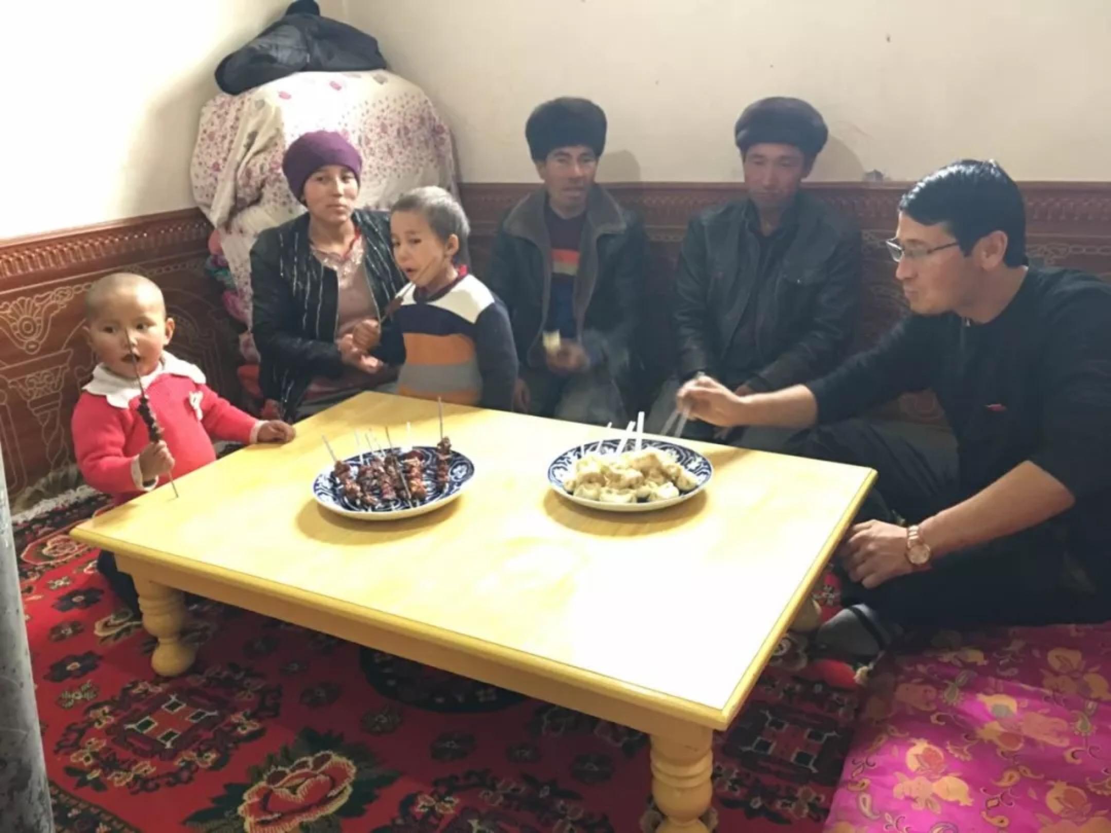 Xinjiang Communist Youth League—WeChat Ziyarete gönderilen bir Han memuru, onlara hediye olarak verdikleri bir masada Uygur ailesiyle birlikte yemek yiyor. Bu görüntü Sincan Komünist Gençlik Ligi tarafından sosyal medya platformu WeChat'ta yayınlandı.