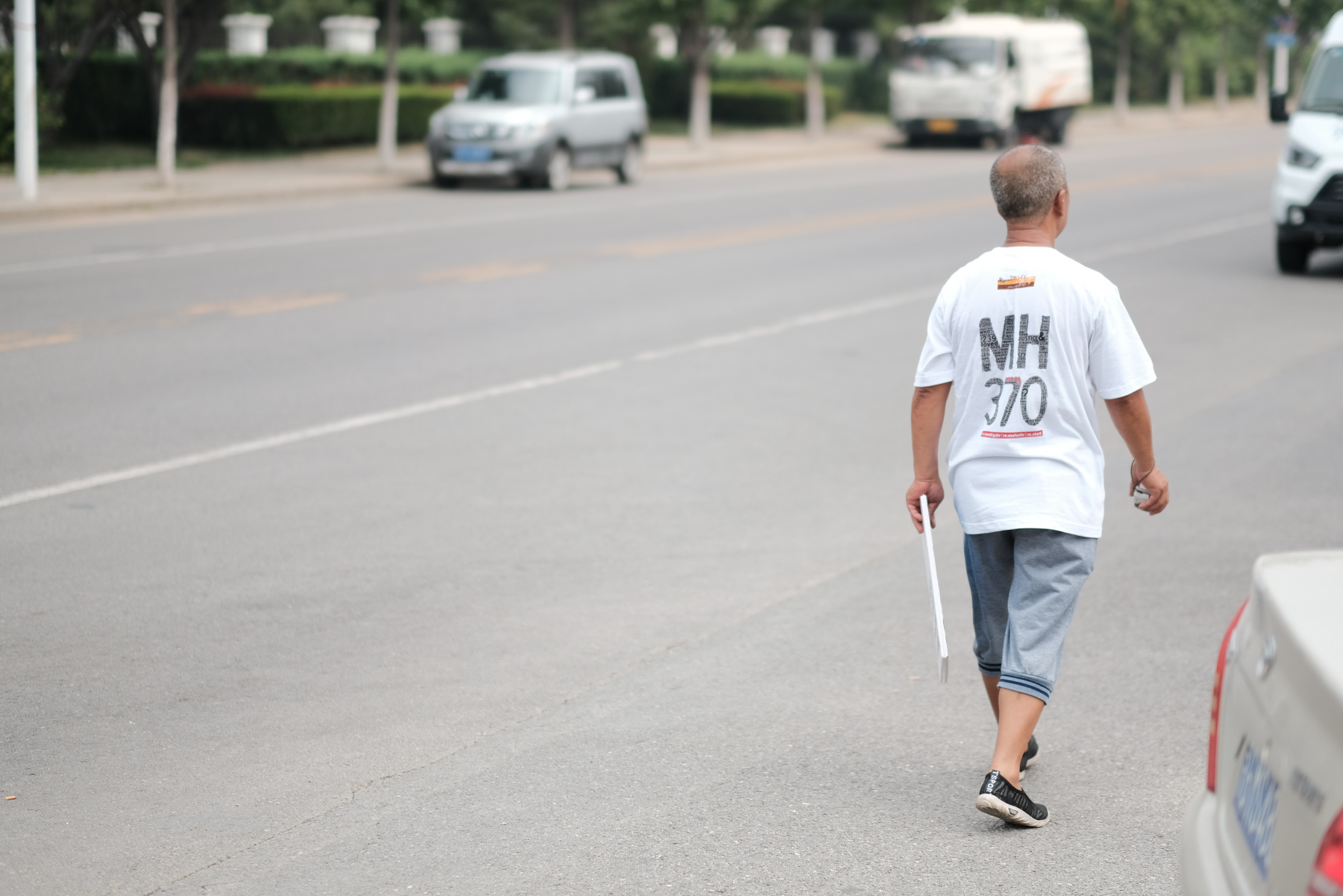 A relative of a passenger on the missing Malaysia Airlines Flight MH370 walks on the street before a press conference held by the Malaysian investigation team, in Beijing, August 3. In May, the last search effort for the flight that went missing four years ago ended without any new findings. (ImagineChina)