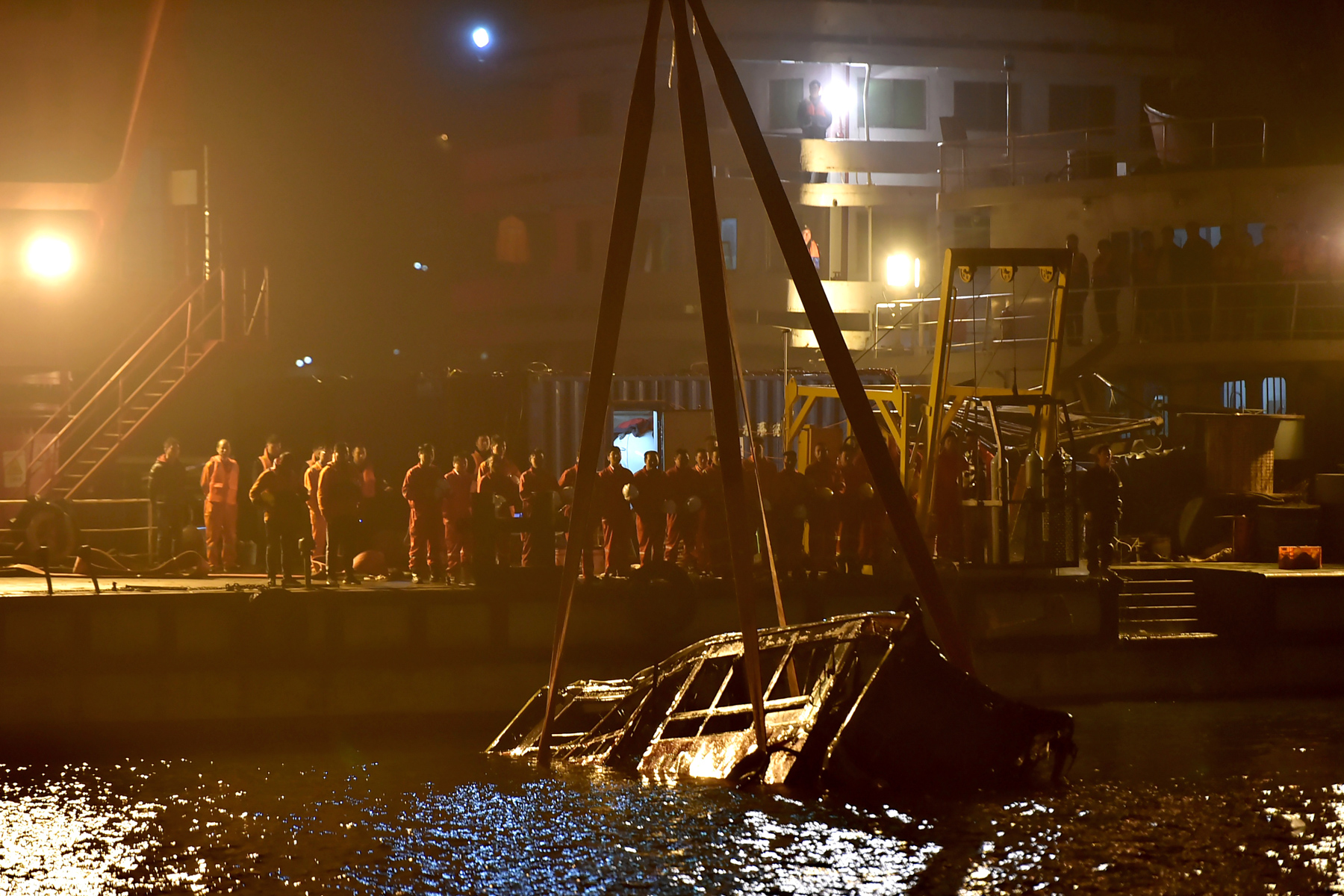 Rescuers watch as wreckage of a bus is lifted out of the Yangtze River in Wanzhou, Chongqing, October 31. The bus crashed and plunged into the river, leaving no survivors. A video released by the police shows that a passenger attacked the driver after she missed her stop and the driver refused to let her off halfway. The driver fought back and lost control of the bus. All 15 people, including the passenger and driver, died in the crash. (Chinatopix via AP Photo)