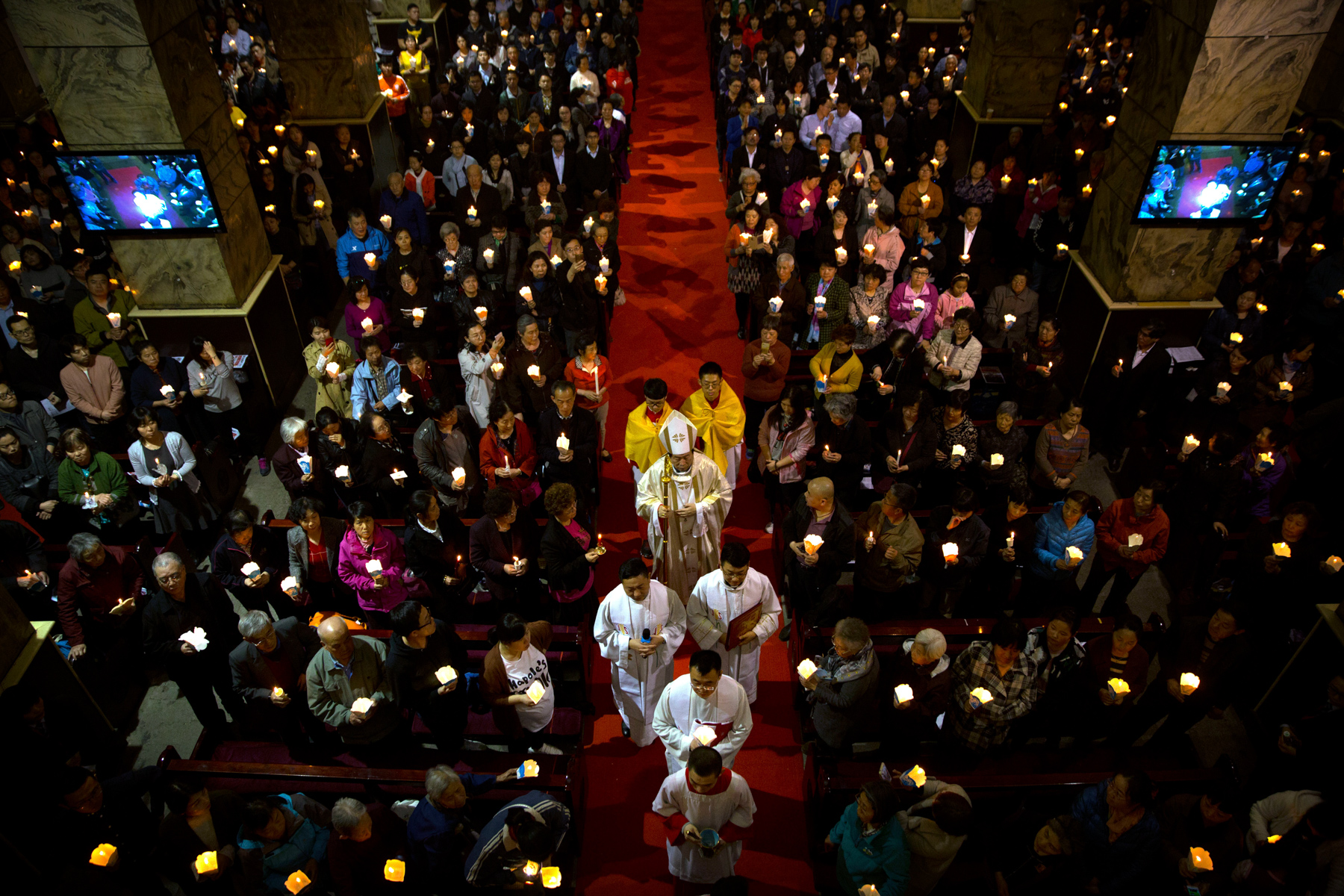 "Chinese Bishop Joseph Li Shan, center, walks down the aisle during a Holy Saturday mass on the evening before Easter at the Cathedral of the Immaculate Conception, a government-sanctioned Catholic church in Beijing, March 31. In September, the Vatican signed a controversial deal with China acknowledging the Chinese Communist Party's power to nominate bishops. Meanwhile, the government ramped up its policing of ""unauthorized"" Protestant churches. (Mark Schiefelbein/AP Photo)"