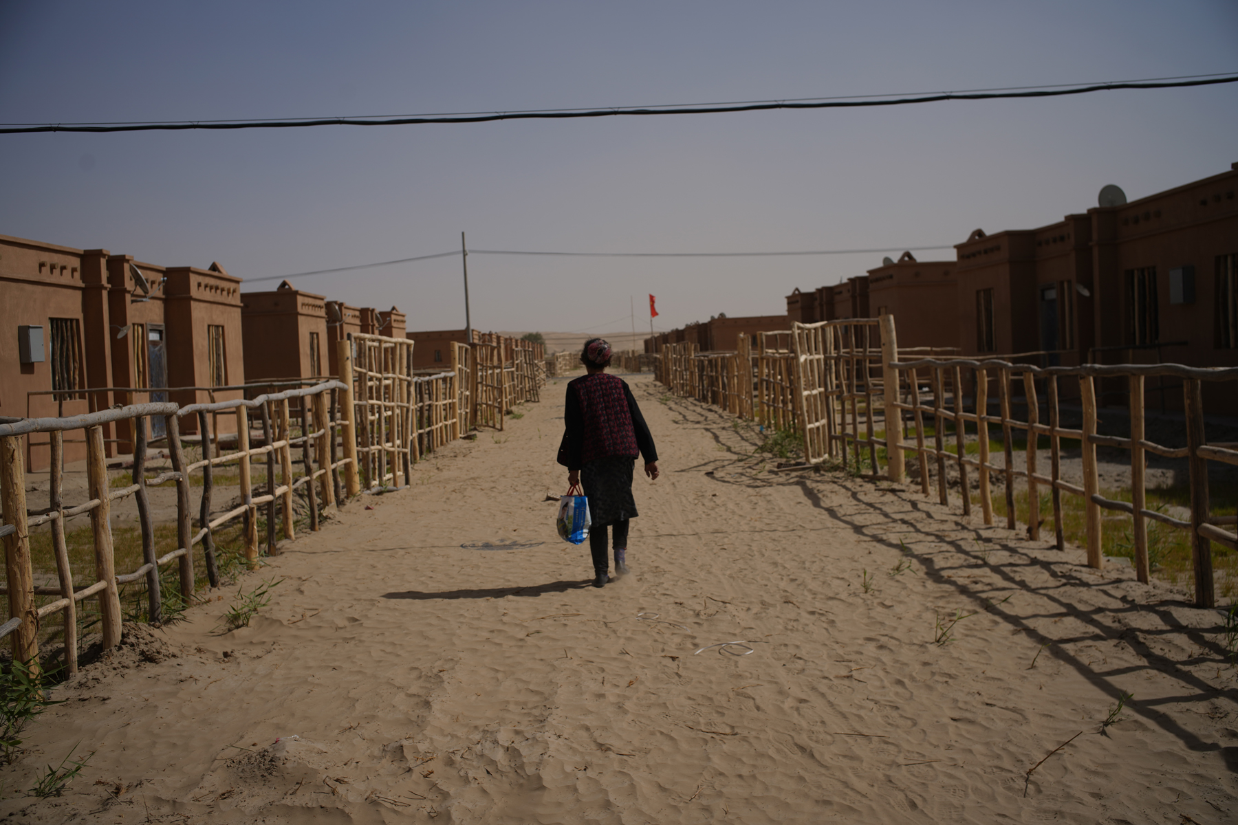 A Uighur woman walks through a new town constructed to house people relocated from a remote village, as part of a national poverty alleviation program, in Xinjiang Uighur Autonomous Region, October 4. Authorities in Xinjiang have incarcerated some one million Uighurs as part of a campaign of religious and cultural repression China's government construes as a method for preventing terrorism. (Chen Jie for ChinaFile)
