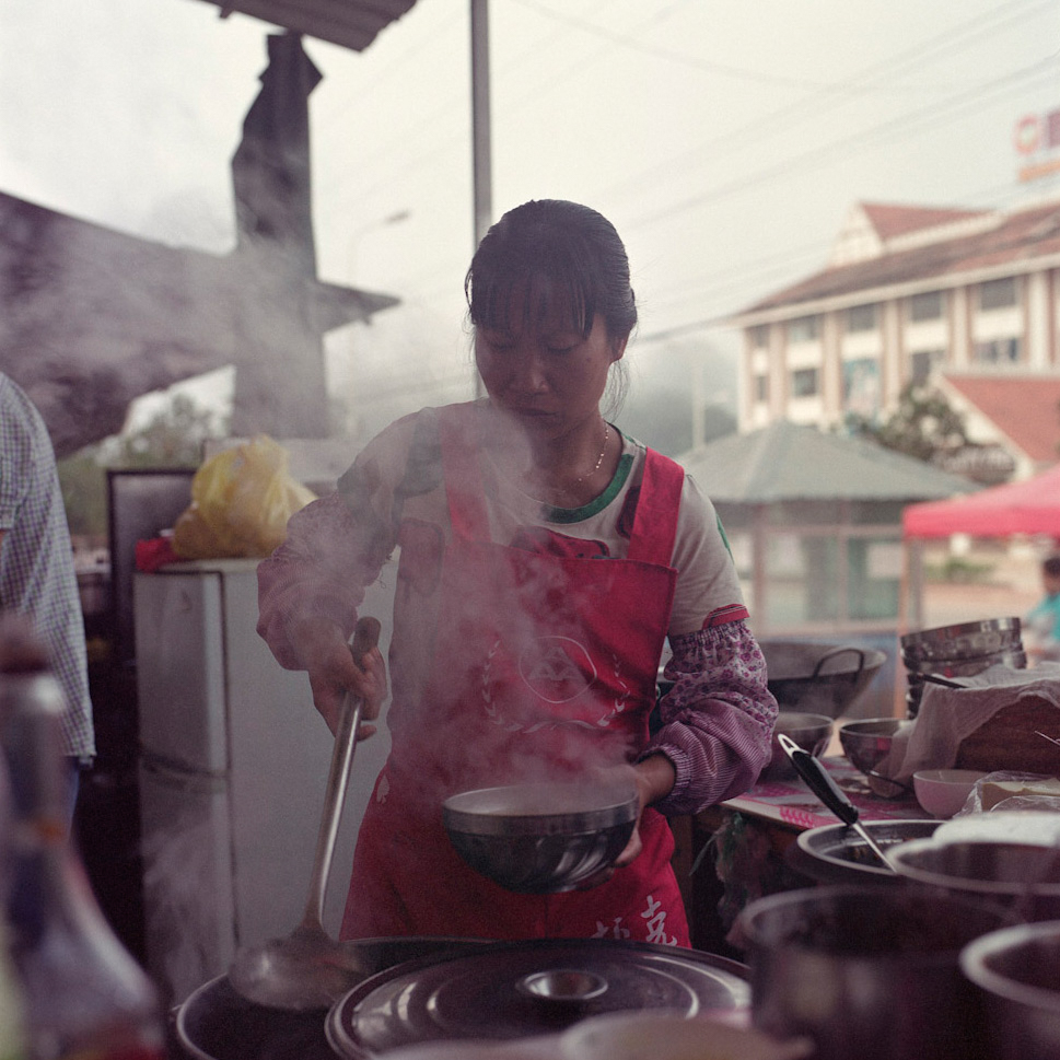 A Chinese woman prepares a bowl of noodles along the main road of Boten, January 2016.