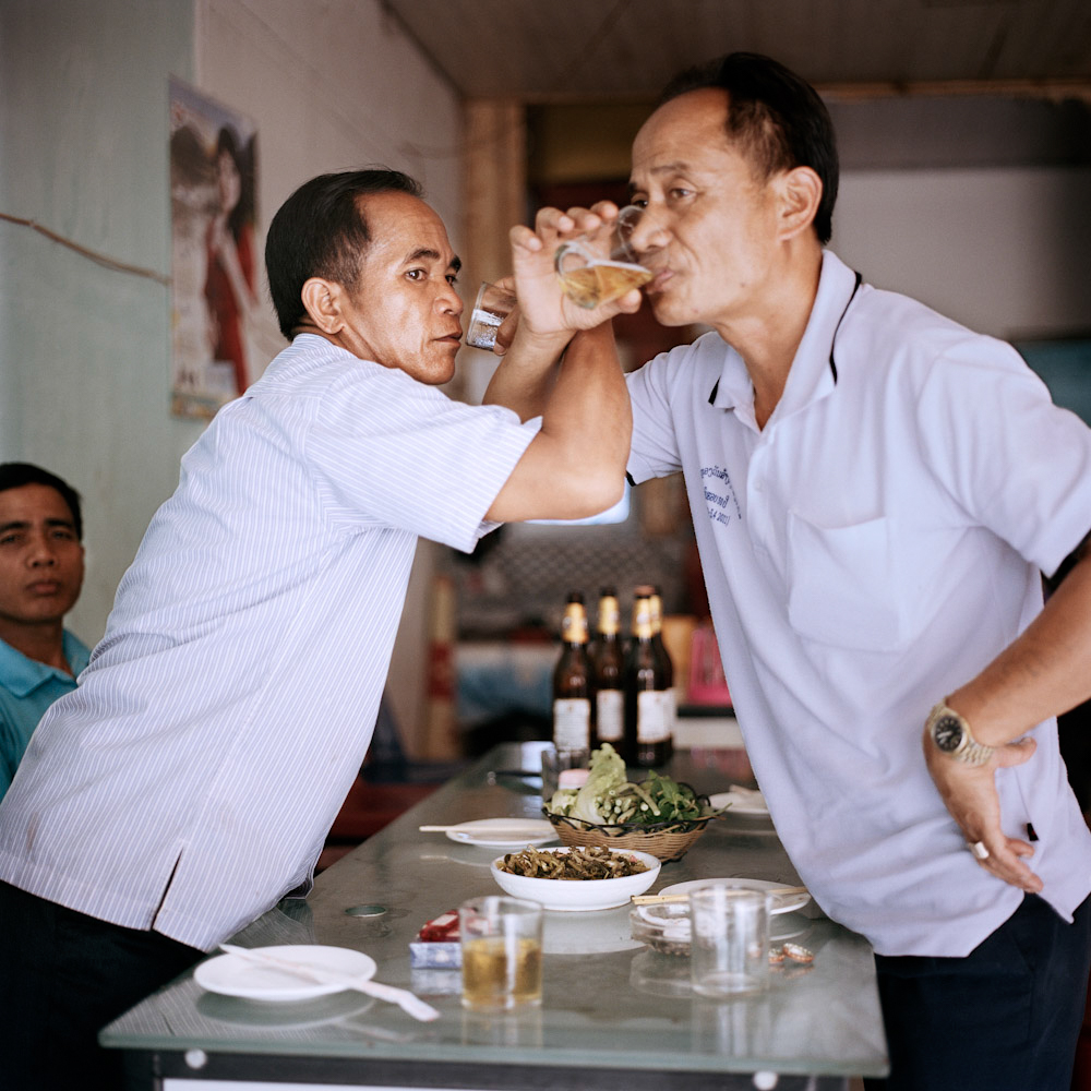 Lao customs officers drink at a restaurant in Boten, May 2013. Lao make up a small percentage of residents in Boten.