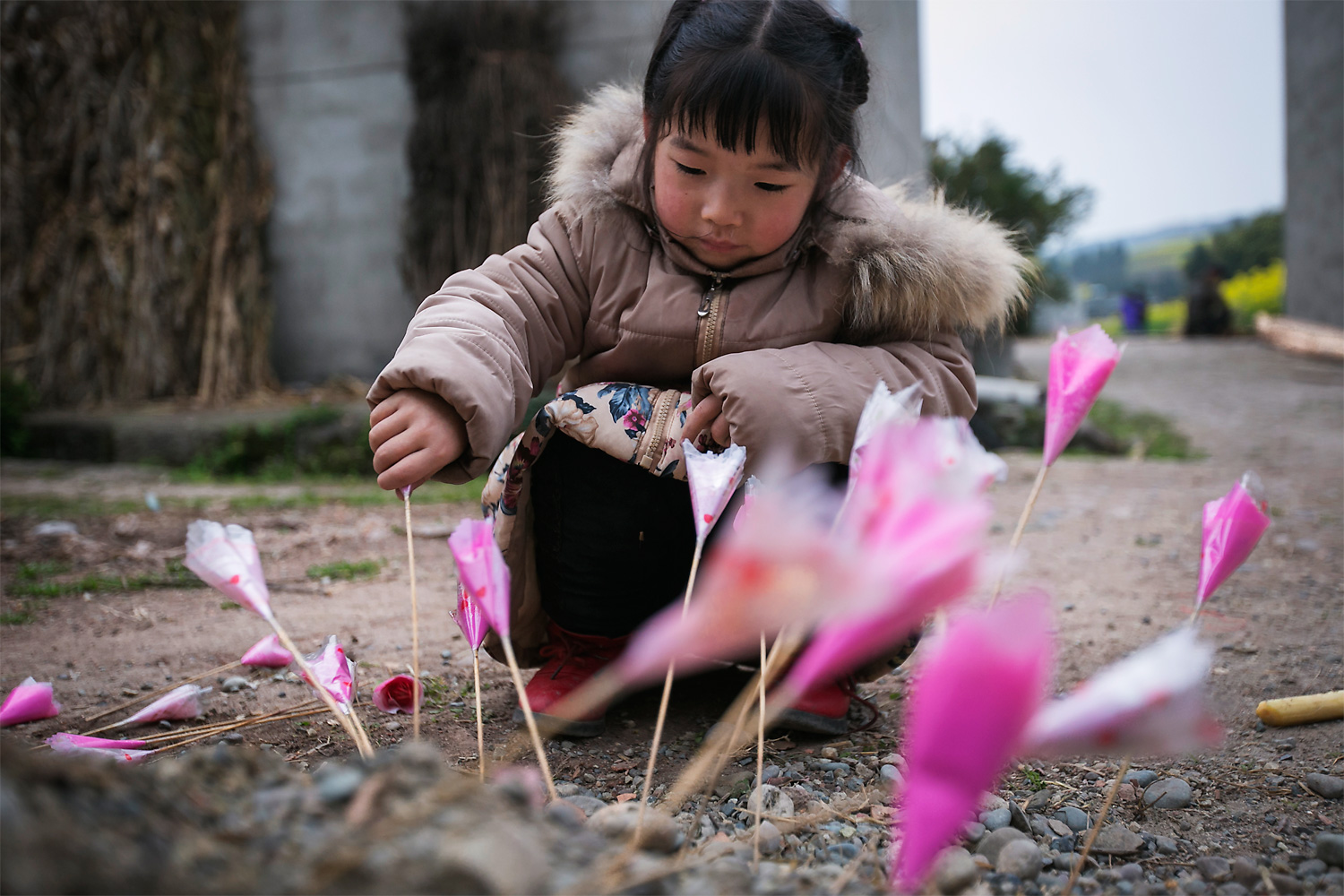Mengmeng, four, sticks fake flowers into the ground in front her home, in Longjing village, March 5, 2015. She cries often. According to Ning Xianfang, she started talking when she was two years old.